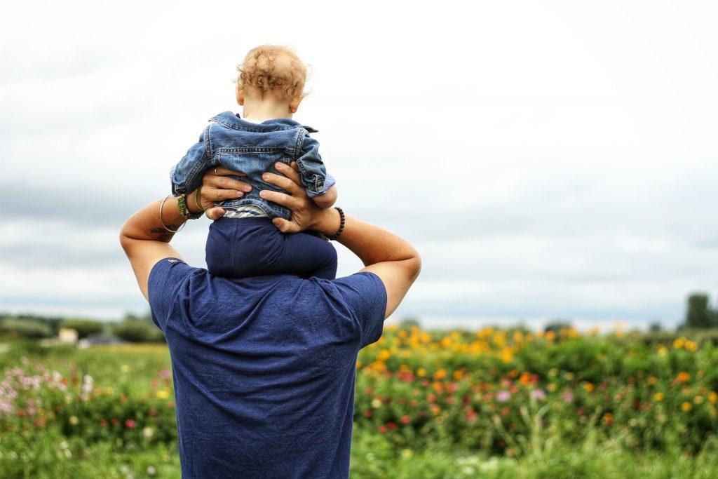 Mężczyna z dzieckiem na ramionach